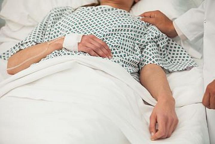 Heath care worker placing a hand on the shoulder of a sick patient in bed.