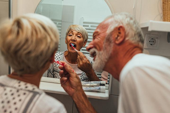 Elderly man brushing wife's teeth