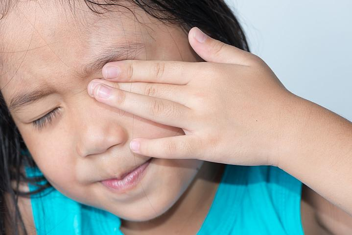 Young girl rubbing her eye