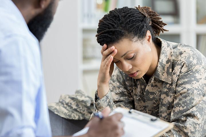 Female military veteran holding her head in an appointment with a health care professional