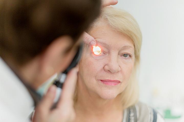 Eye doctor giving an older woman an eye exam