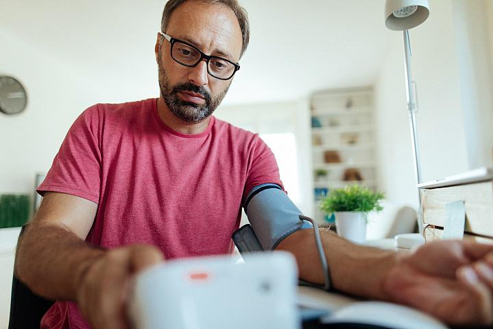 Man checking his blood pressure at home