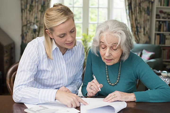 Woman helping older adult with paperwork