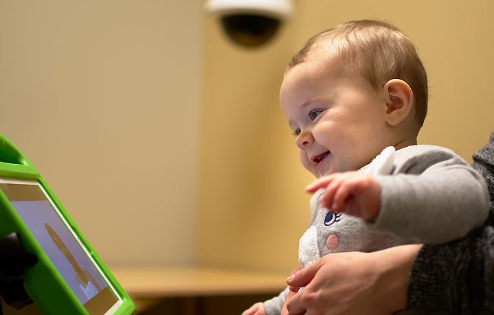 Smiling toddler looking at person on tablet screen