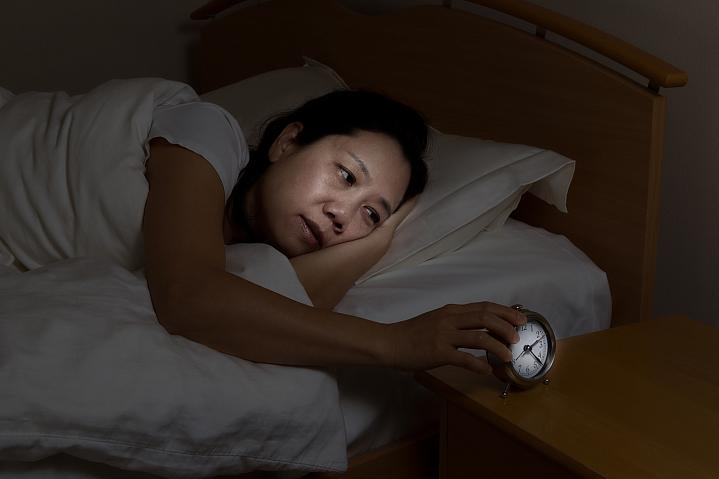 Woman awake in bed touching the alarm clock