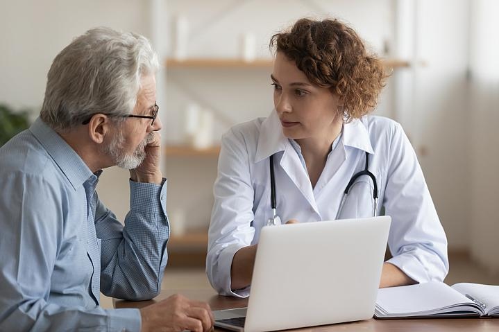 Female doctor talking with older male patient
